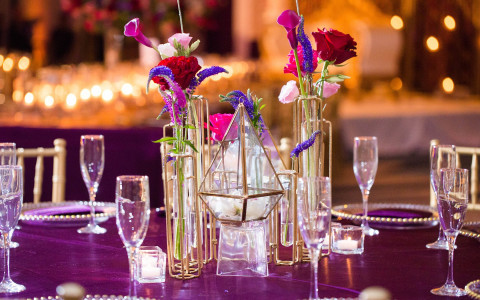 Close up of glasses on table with purple tablecloth