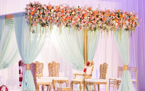 Gold chairs on stage with white canopy and rose decor