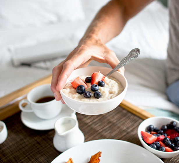 man handing oatmeal to someone in bed