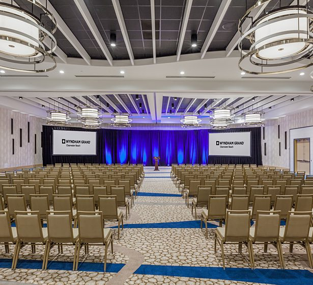 Conference room with rows of chairs, stage and two projection screens