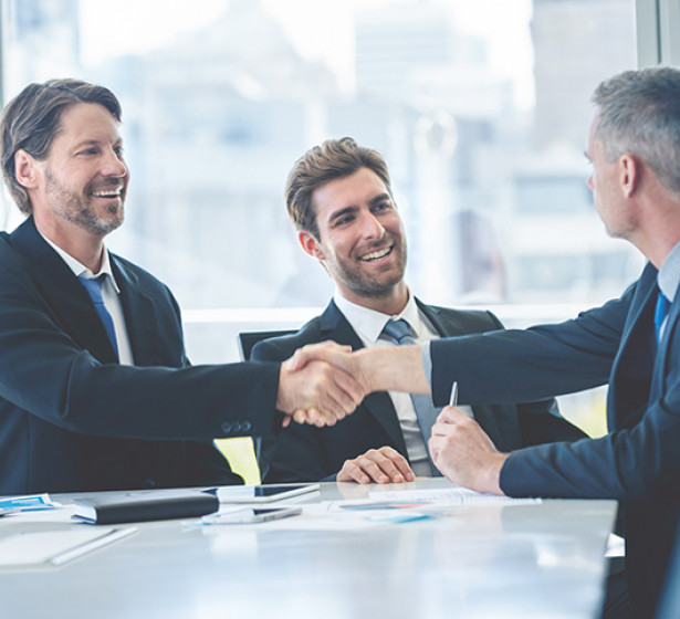 man shaking another mans hand during a board meeting