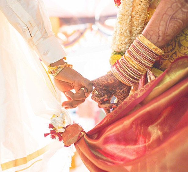 women holding hands during an indian wedding