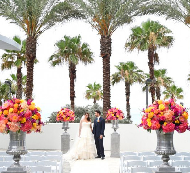 Wedding couple surrounded by colorful flower bouquets and palm trees in the back