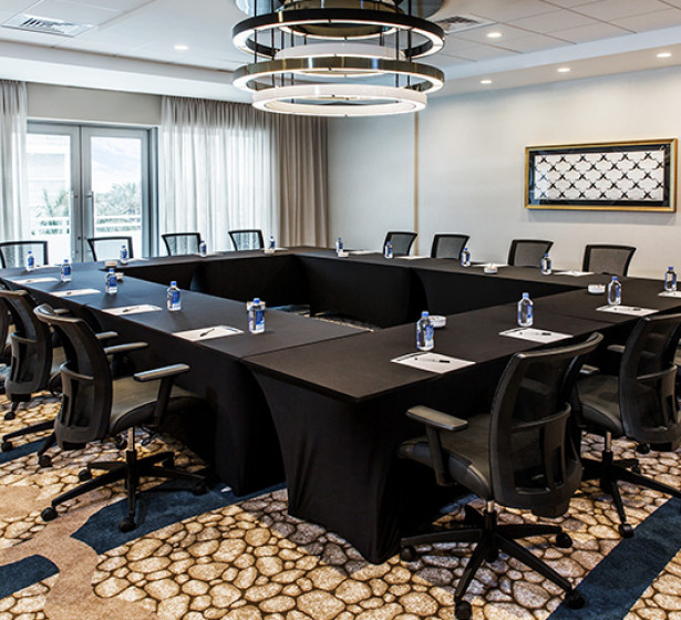 black tables with water bottles and setup in a board room