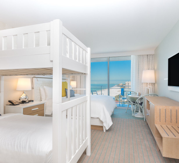 white bunk beds in a bedroom overlooking water