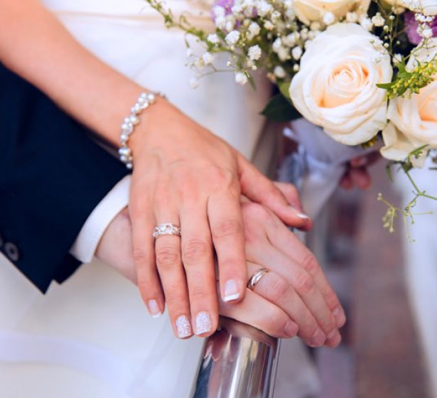 Close up of wedding couple hands on top of bouquet