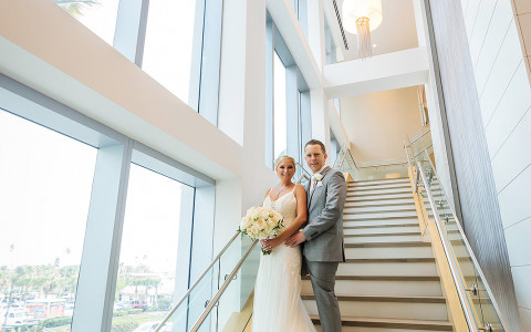 bride posing with groom on an open stairwell