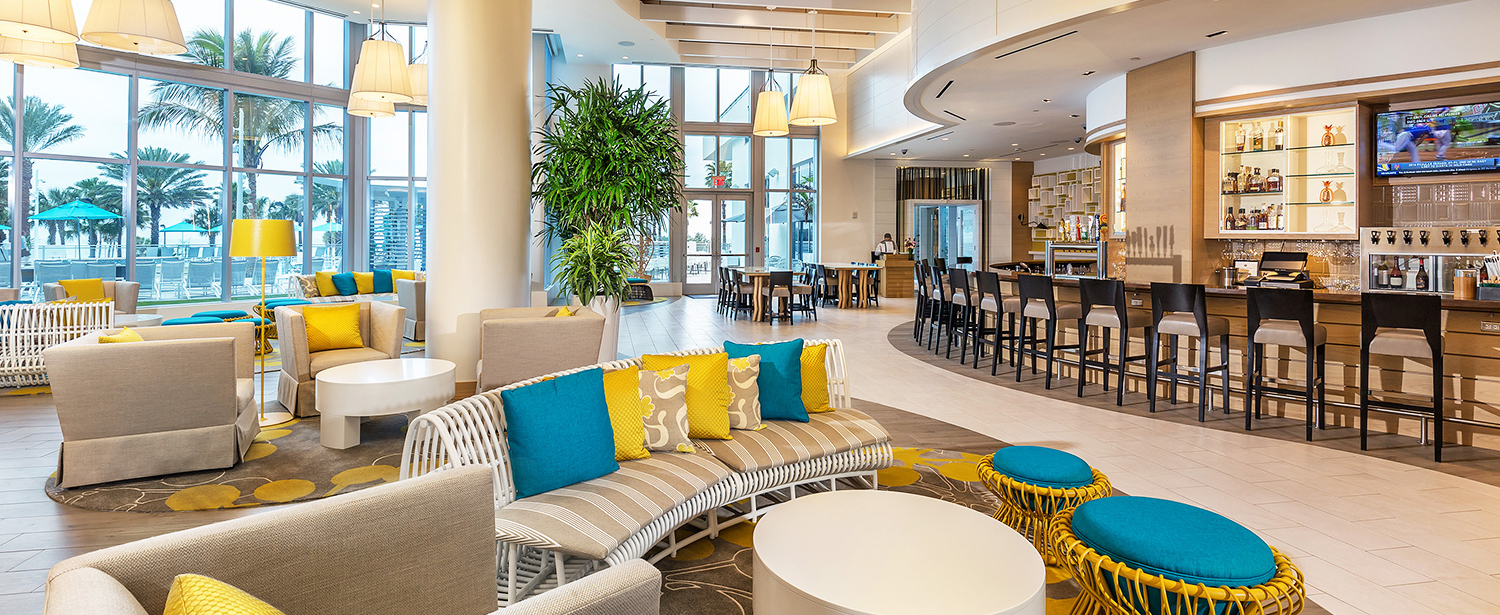 Lobby with wicker seating, colorful pillows & bar in the back