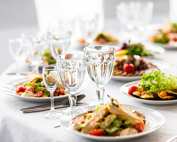 table set with plate of colorful foods and glassware