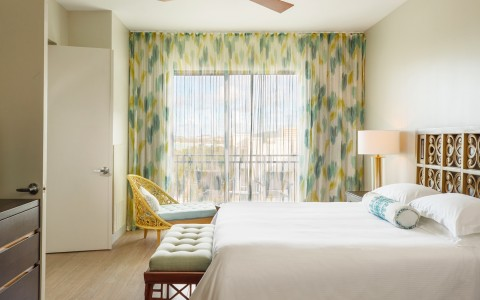 bedroom with white linens and turquoise and yellow curtains and chair