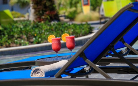 pool chair with 2 strawberry daiquiris