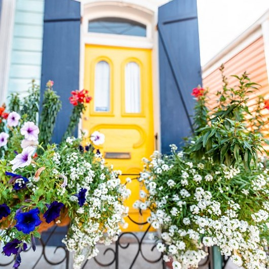 house with a yellow door and flowers