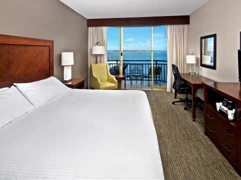Guest room with view to bay and large bed with white linen