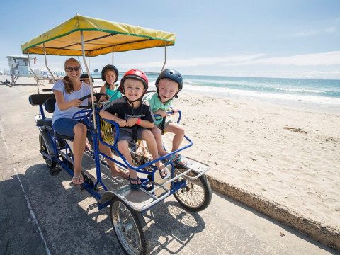 Family biking by the beach on a sunny day