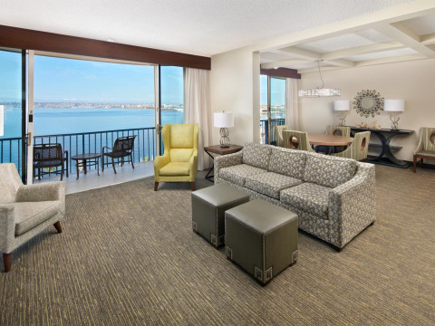 guest room with seating area and balcony view to the bay
