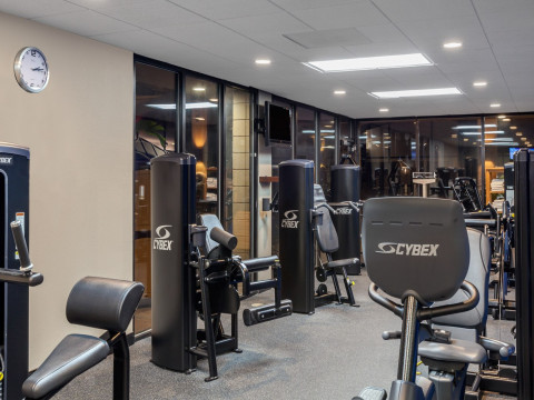 Hotel gym with exercise equipment and mirrors