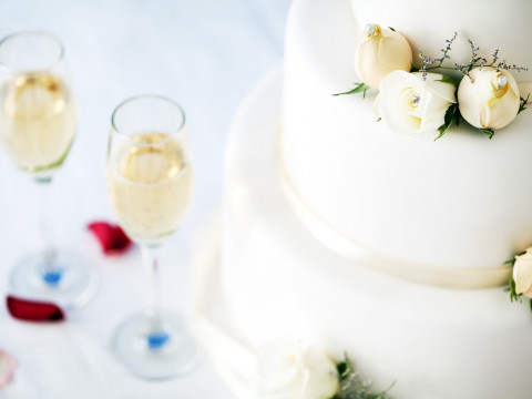 White wedding cake adorned with roses with champagne flutes