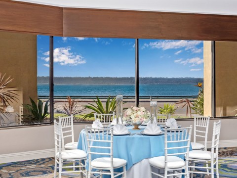 Harborside venue space with white and blue table set up with views to the sea
