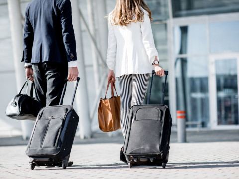 Business travelers pulling luggage