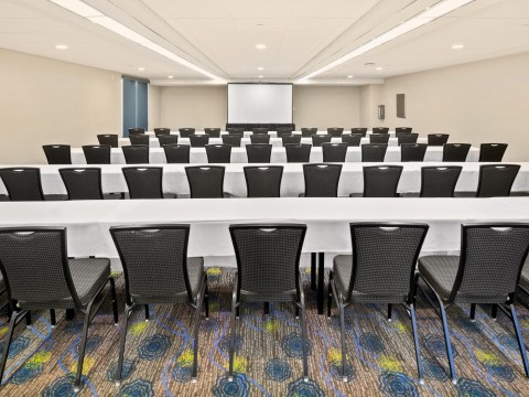 Bay Room meeting space with tables, chairs and a screen