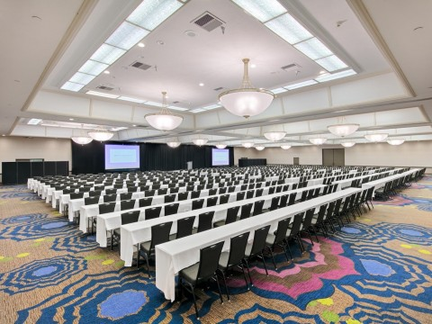 Pacific Ballroom meeting space with two screens, tables and chairs