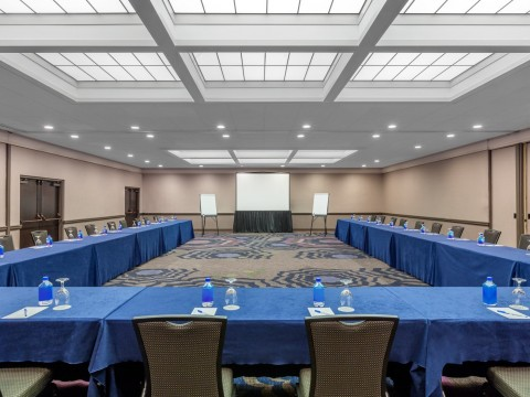 Coast Ballroom meeting space with a screen and tables