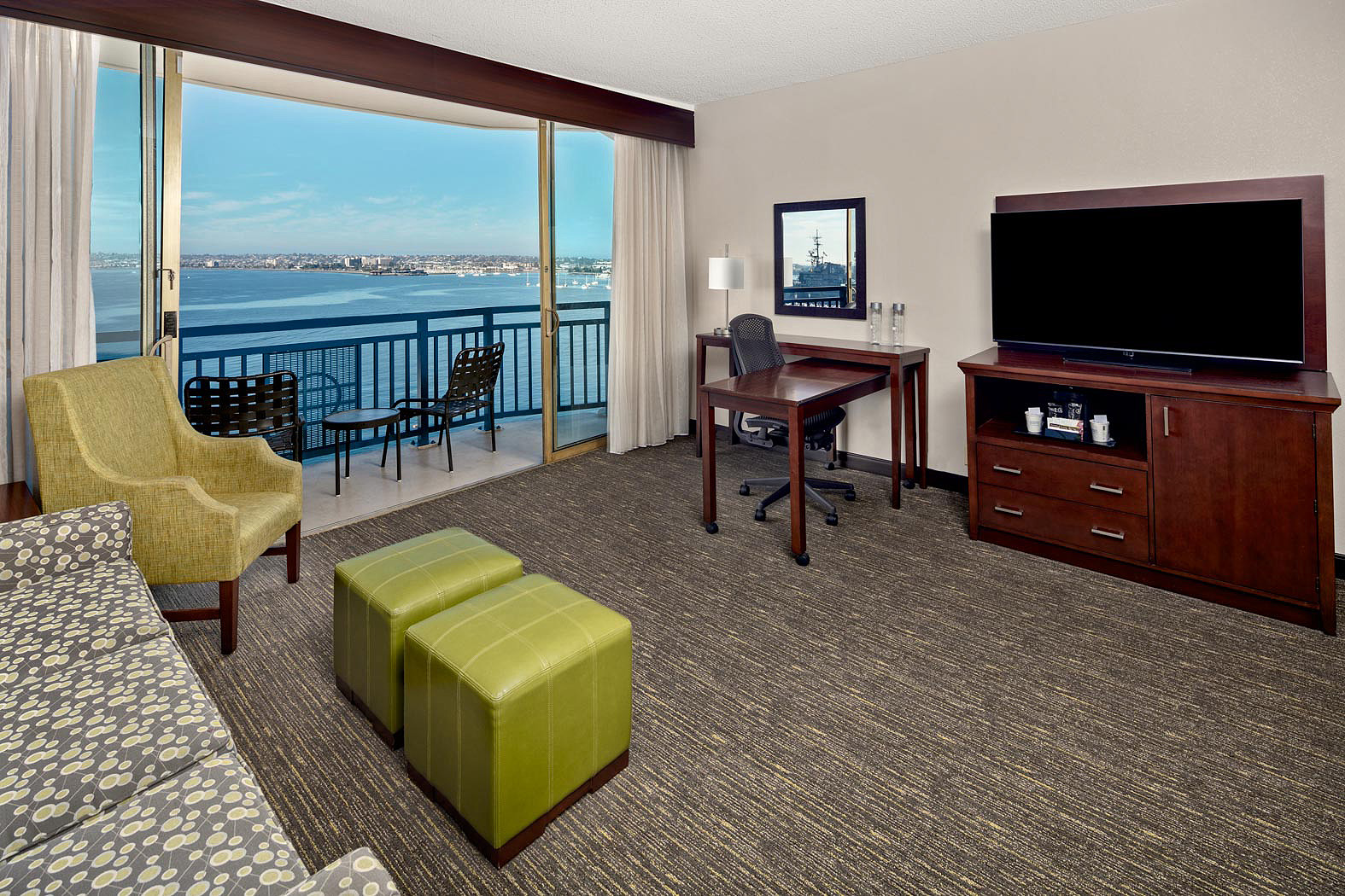 Guest room seating area with couch and chair with view to San Diego Bay