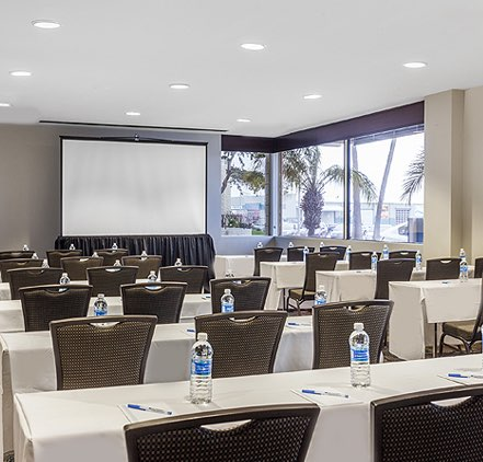Embarcadero Room setup for a meeting with tables and chairs and a projector screen