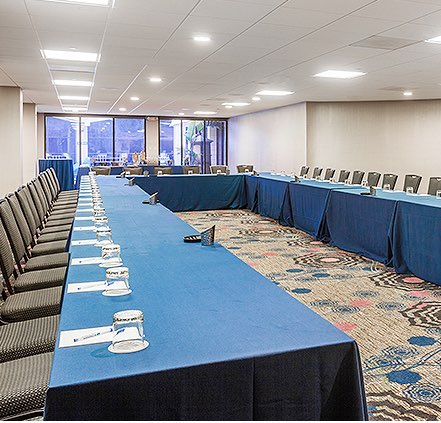 Porthole room setup with long tables an chairs for meeting