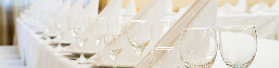 Wine glasses lined up on a white table cloth