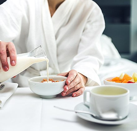Guest enjoying room service breakfast in a robe