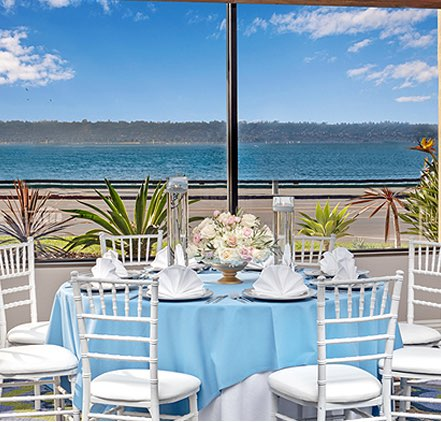Harborside room with round table and white chairs looking out to bay and blue sky