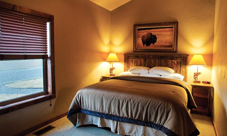Queen bed with two nightstands with lamps and a rustic photo of a buffalo over the bed
