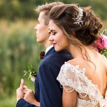 Bride hugging groom from behind outdoors