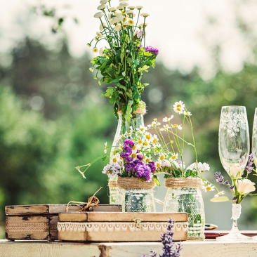 Rustic flower centerpieces and champagne flutes on a table outside