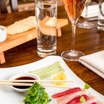 Sashimi combo plate, glass of water, glass of wine and platter of bread and butter