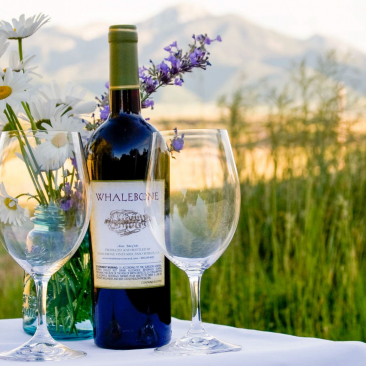 Bottle of wine, two wine glasses and white and purple flowers on a table outside in the mountains