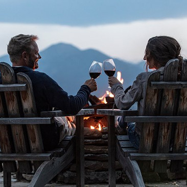 couple toasting with wine glasses while looking at mountains