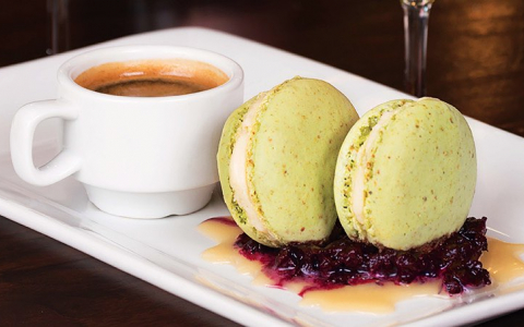 Two green macaroons and a cup of espresso