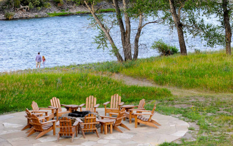 wooden lawn easy chairs around a fire-pit overlooking the river