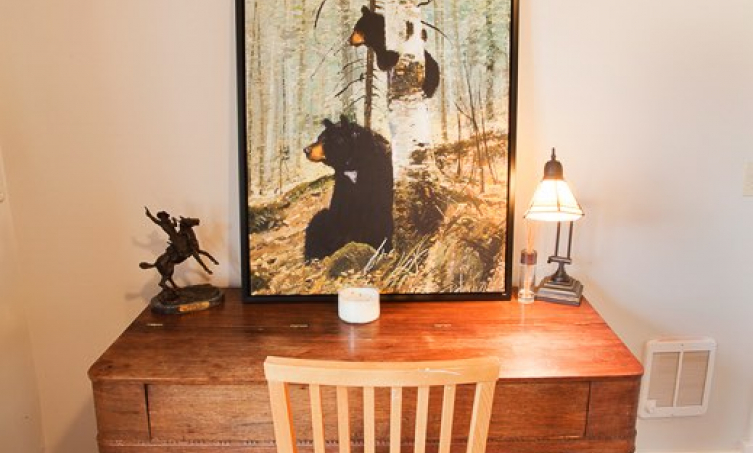 Chair and desk topped with a lamp and large painting of two bears in the woods