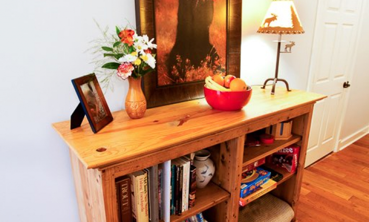 Bookcase filled with books and games, topped with a lamp, bowl of fruit, large painting of a bear, a vase and a picture frame