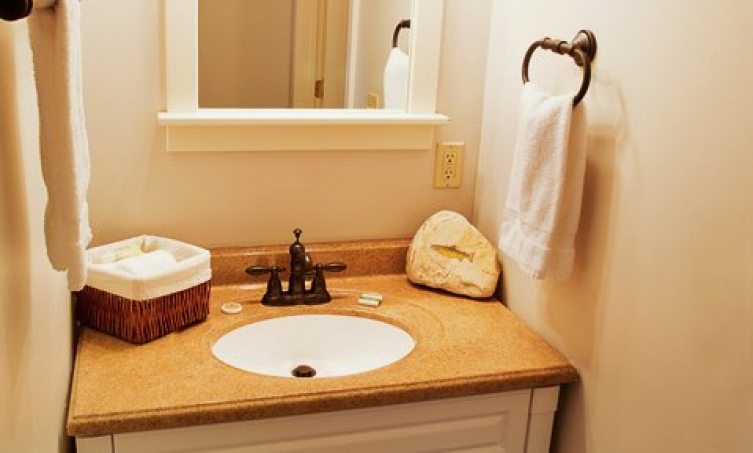 White and tan bathroom vanity with sink, mirror and hand towels