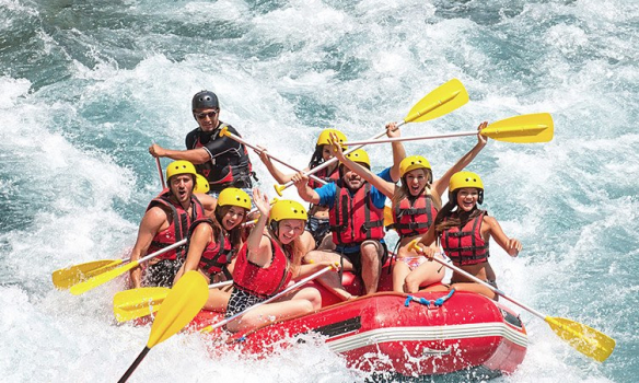 Group of people in helmets white water rafting