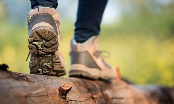 Close up shot of hiking shoes walking across a wooden log