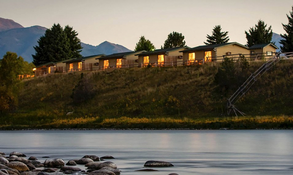 Row of cabins on top of a hill in the mountains behind a river