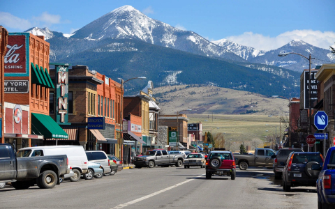 Row of shops in front of mountains in the town of Livingston Montana with cars driving down the road