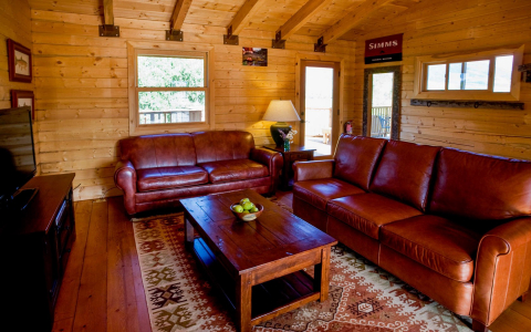 Living area in a cabin with couch, love seat, coffee table and television entertainment center