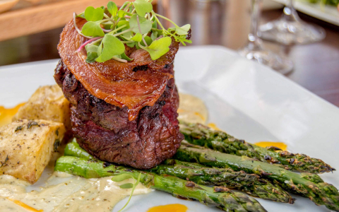 Plate of steak topped with bacon with potatoes and asparagus