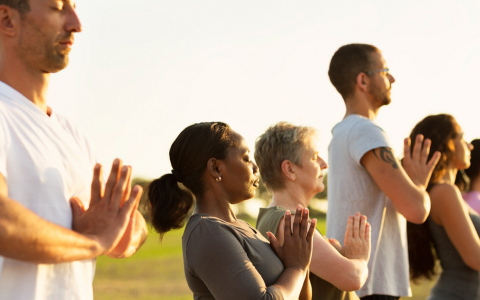 Row of five people with their eyes closed and hands placed together practicing yoga